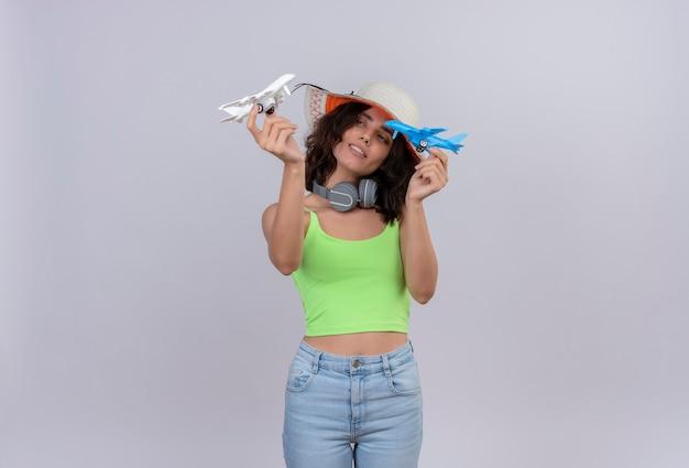 Уверенная в себе молодая женщина с короткими волосами в зеленом топе в наушниках в шляпе от солнца держит в руках сине-белые игрушечные самолетики на белом фоне