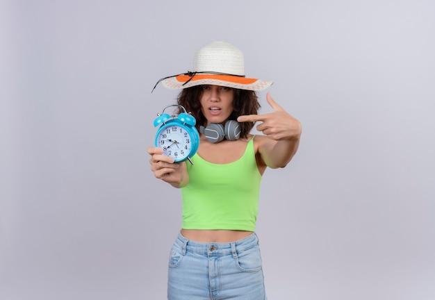 Уверенная в себе молодая женщина с короткими волосами в зеленом топе в шляпе от солнца, указывая указательным пальцем на синий будильник на белом фоне