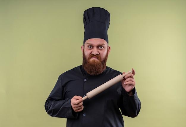 緑の壁を見ながら麺棒を見せている黒い制服を着た混乱したひげを生やしたシェフの男