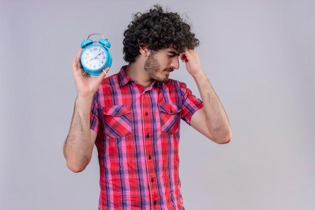 Смущенный красавец с вьющимися волосами в клетчатой рубашке держит руку за голову и держит синий будильник