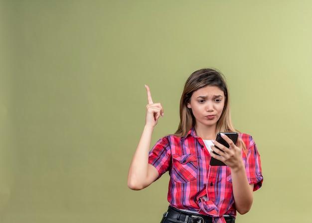 Смущенная милая молодая женщина в клетчатой рубашке смотрит на мобильный телефон и поднимает руку на зеленой стене