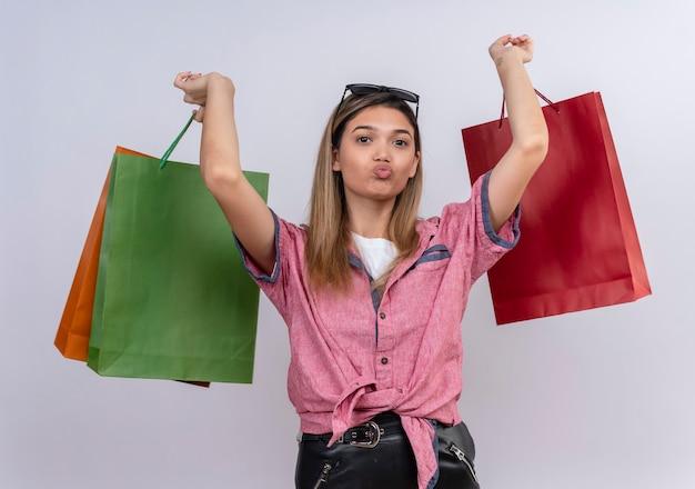 흰 벽을 보면서 화려한 쇼핑 가방을 들고 빨간 셔츠를 입고 혼란 젊은 여자