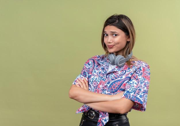 Смущенная молодая женщина с длинными волосами в рубашке с принтом пейсли в наушниках держится за руки