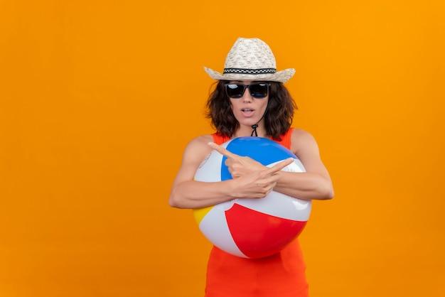 何かを指している膨脹可能なカラフルなボールを保持している太陽の帽子とサングラスを身に着けているオレンジ色のシャツの短い髪の混乱した若い女性