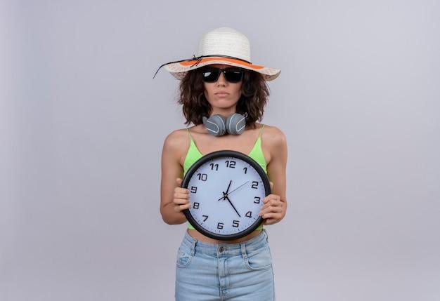 Смущенная молодая женщина с короткими волосами в зеленом топе в солнечных очках и шляпе от солнца держит настенные часы на белом фоне