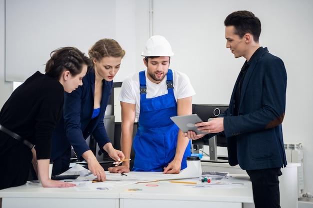 建設設計チームが会議室でブレーンストーミングを行い、新鮮なアイデアや新しいアプローチを模索しています