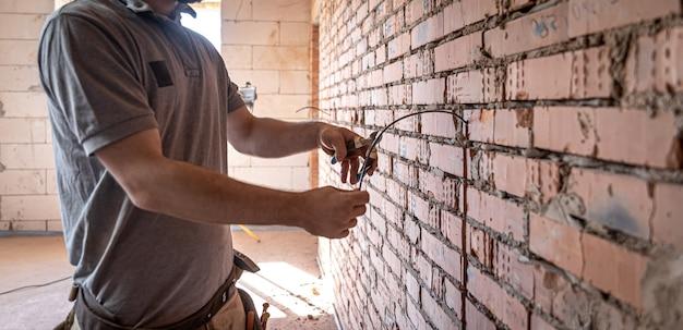 Электрик-строитель перерезает кабель напряжения во время ремонта.