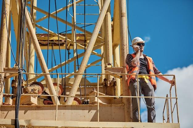 Инженер-строитель в клетчатой рубашке, оранжевом жилете и белой каске на желтом строительном кране с рацией в руках. бригадир, начальник, рабочий
