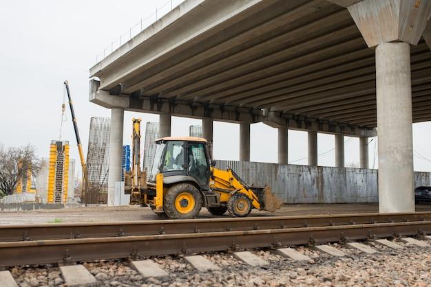건설 굴삭기가 건설중인 철근 콘크리트 도로 교량 아래를지나갑니다.
