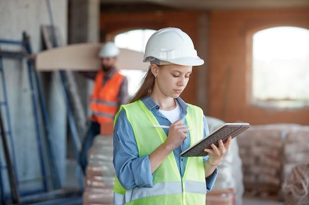 Инженер по обслуживанию строительной отрасли - симпатичная женщина в униформе и защитном шлеме с планшетом в руках против строительной площадки и рабочего.