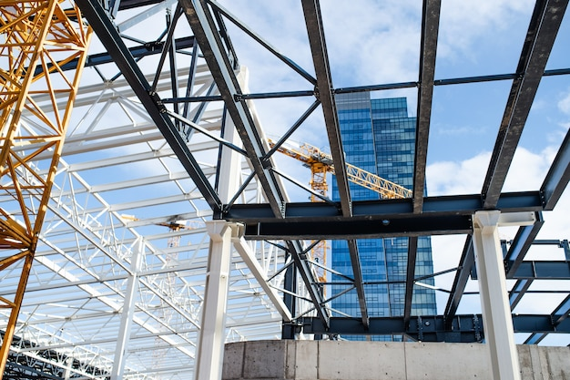 Строительная площадка со стальной рамной конструкцией и краном.
