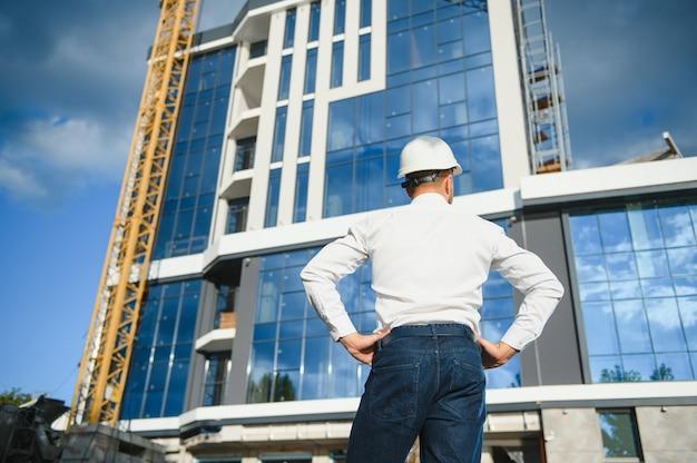 建設作業員は、建設現場と日没の背景に注ぐコンクリートポンプを制御します