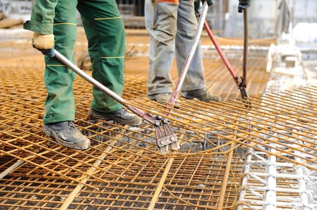 Строительный рабочий, соединяющий железные балки