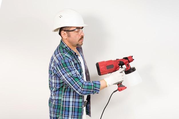 보호 헬멧과 고글을 쓴 건설 노동자가 전기 스프레이 건으로 벽을 칠합니다.