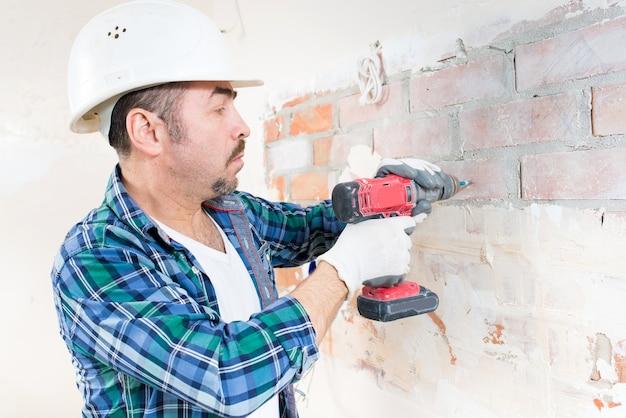 보호 헬멧의 건설 노동자가 전기 드라이버로 벽에 나사를 조이고 있습니다.