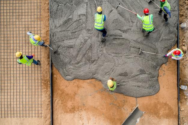 도로 건설 현장에서 젖은 콘크리트를 붓는 건설 노동자
