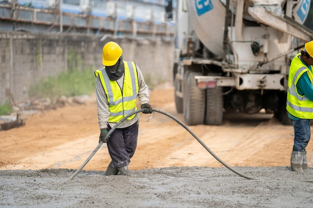 Строительный рабочий заливает мокрый бетон на дорожно-строительной площадке