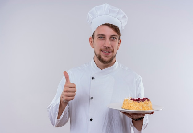 흰색 밥솥 유니폼과 샐러드와 함께 접시를 들고 흰 벽을 보면서 엄지 손가락을 보여주는 모자를 쓰고 콘텐츠 잘 생긴 젊은 수염 난 요리사 남자