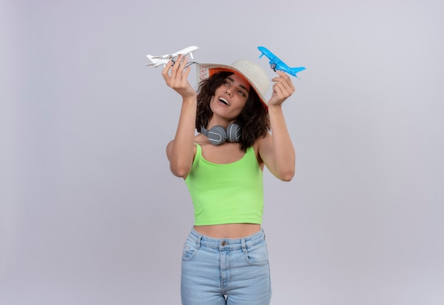Довольная молодая женщина с короткими волосами в зеленом топе в шляпе от солнца держит сине-белые игрушечные самолетики на белом фоне