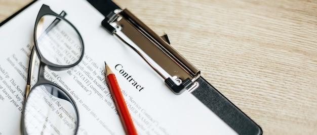 Контракт на деревянном рабочем столе с очками и красным карандашом. документы готовы к подписанию. бизнес-концепция. соглашение о сотрудничестве.