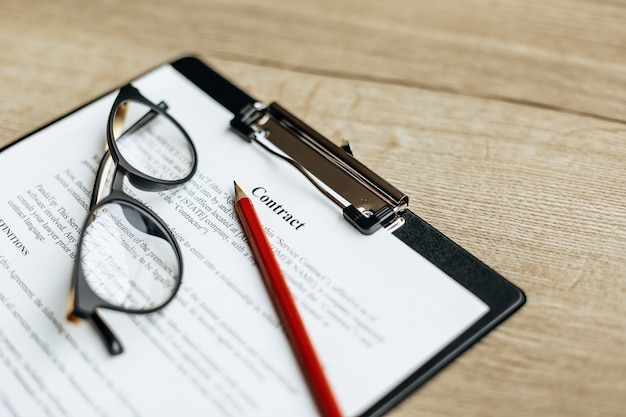 안경과 빨간 연필로 나무 작업 테이블에 대한 계약