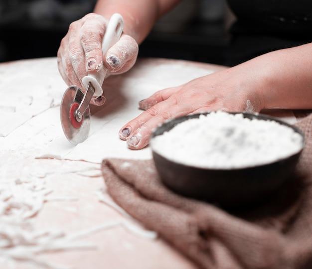 黒いボウルにラビオリ生地、小麦粉を切る料理人