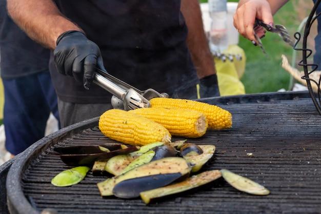 Повар жарит кукурузу и овощи на угольном гриле.