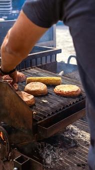 옥수수 개 암 나무 열매와 햄버거 빵을 그릴에 튀기는 요리사. 푸드트럭. 길거리 음식