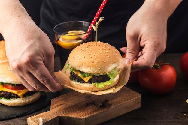 방금 만든 맛있는 쇠고기 햄버거를 들고 있는 요리사