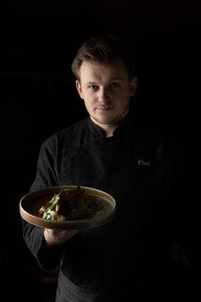 Повар в черной куртке от шеф-повара подает приготовленное блюдо на тарелке