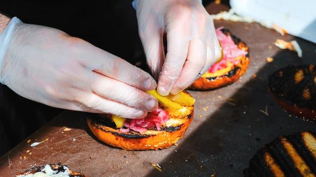 한 요리사가 다양한 재료로 햄버거를 만들고 있습니다. bbq