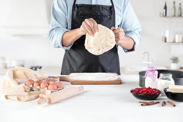 素朴なキッチンで料理人。小麦粉製品や生地、パン、マフィン、パイ、ケーキ、ピザを調理するための食材を使った男性の手