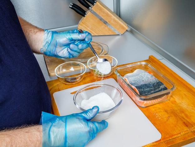 위생 장갑을 낀 요리사가 연어 필레를 소금에 절이기 위해 혼합물을 준비합니다.