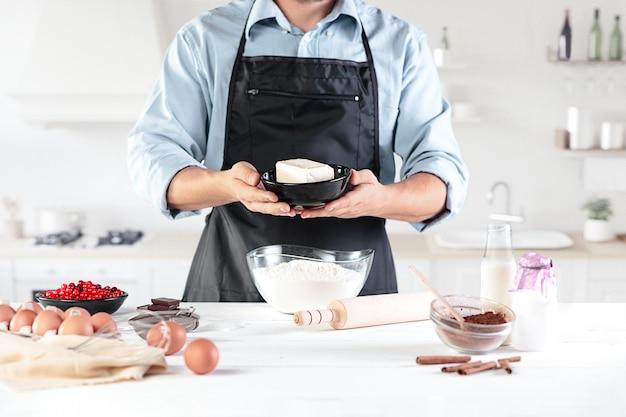 Повар с яйцами на деревенской кухне на фоне мужских рук