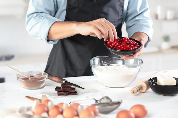 Повар с яйцами на деревенской кухне у стены мужских рук
