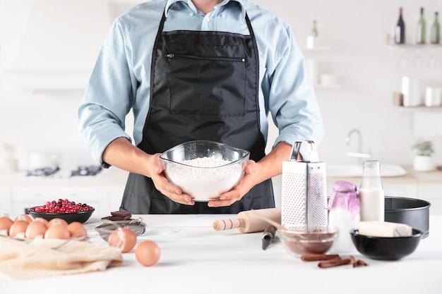 Повар с яйцами на деревенской кухне против мужских рук