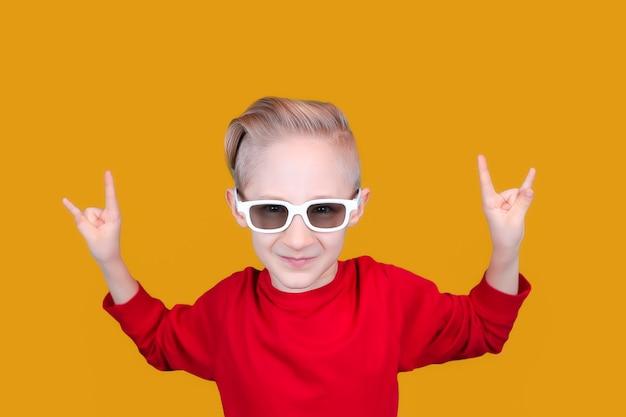 빨간 옷과 안경을 쓴 시원하고 쾌활한 아이가 노란 배경에 손짓을 보여줍니다