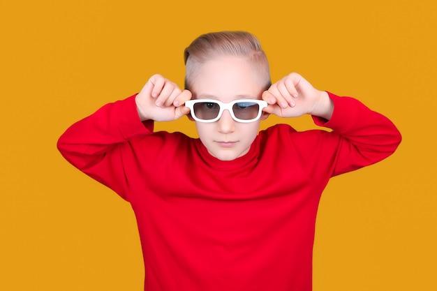 빨간 재킷을 입은 멋진 아이가 노란 배경에서 안경에 손을 얹고 있다