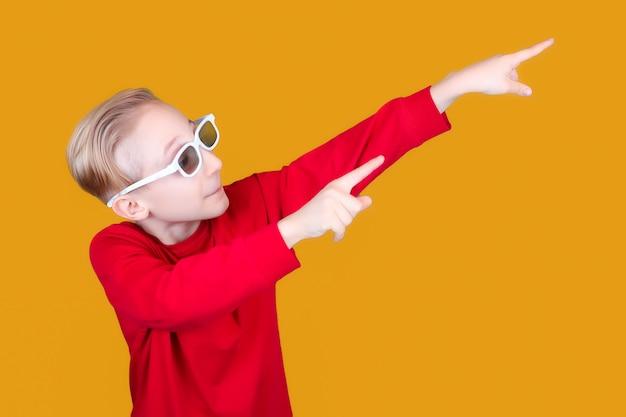 노란색 배경과 어린이용 3d 안경을 쓴 멋진 아이가 손으로 옆으로 방향을 보여줍니다