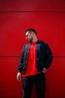 街の赤い建物の近くに、黒のジャケットを着たスタイリッシュな赤いtシャツを着た流行のサングラスをかけたクールな若い男が立っています。魅力的な現代人。ファッショナブルな夏の紳士服。ストリートスタイル
