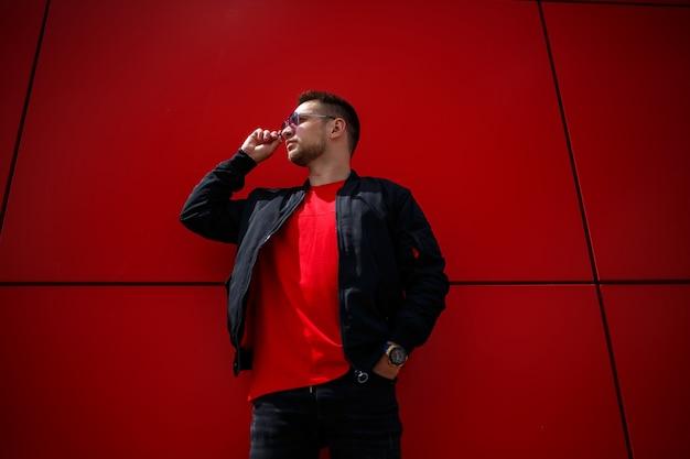 세련된 빨간 티셔츠에 검은색 재킷을 입은 세련된 선글라스를 쓴 멋진 청년이 도시의 빨간 건물 근처에 서 있습니다. 매력적인 현대 남자. 세련된 여름 남성 의류. 스트리트 스타일