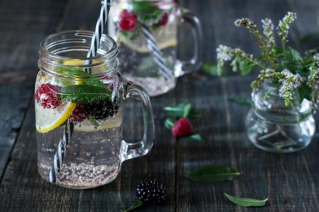 Охлаждающий лимонный напиток в стеклянной чашке на деревянном столе