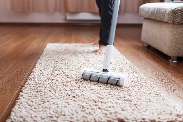 무선 진공 청소기는 거실의 카펫을 현대적인 다리 바닥으로 청소합니다.