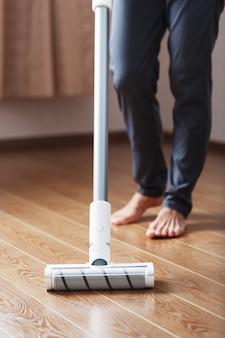 Беспроводной пылесос чистит паркет в гостиной нижней частью ножек.