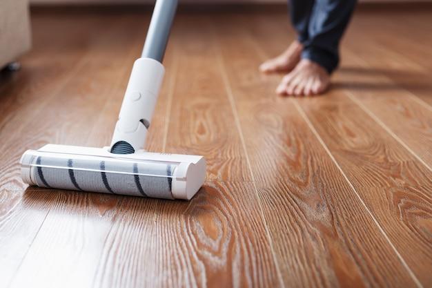 コードレス掃除機は、リビングルームの寄木細工の脚の下部を掃除します。