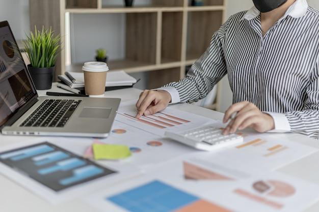 한 기업 금융가가 재무제표의 정확성을 위해 재무 문서를 확인하고 있고, 계산기를 사용하여 문서의 숫자를 확인하여 계산하고 있습니다. 금융 개념입니다.