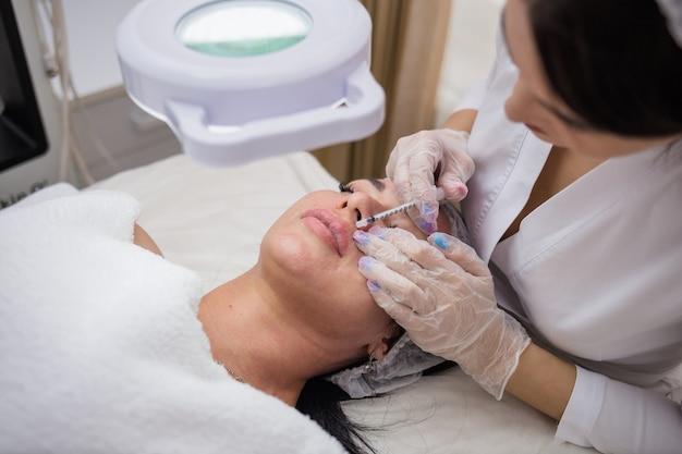 白い制服を着た美容師がクライアントのために唇を増強します