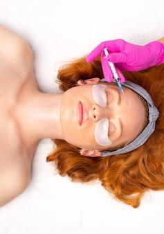 미용사는 미용실에서 아름답고 젊은 여성의 얼굴에 주름을 조이고 부드럽게하기 위해 활력을주는 얼굴 주입 절차를 수행합니다. 스킨 케어 미용.