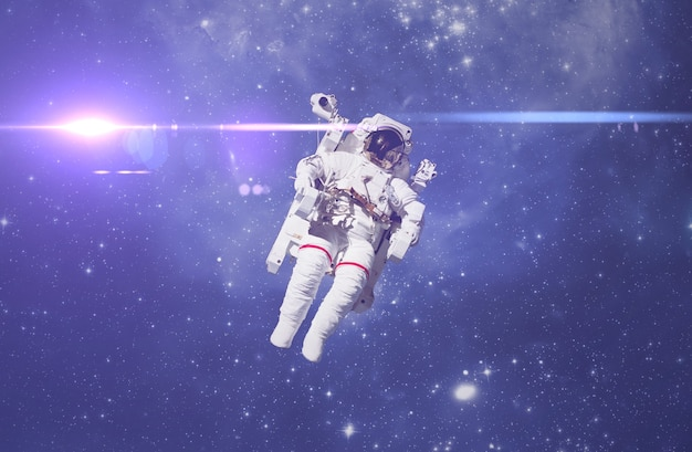 Космонавт летит в космическом пространстве со звездами и фоном галактики со световым лучом. элементы этого изображения предоставлены наса