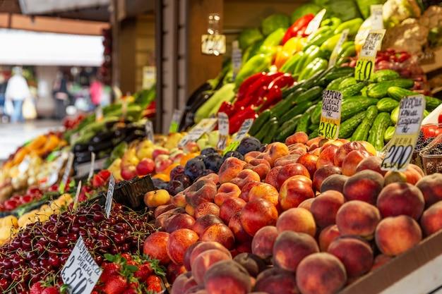 Прилавок с различными спелыми фруктами на рынке. витамины и здоровое питание. вид сбоку.